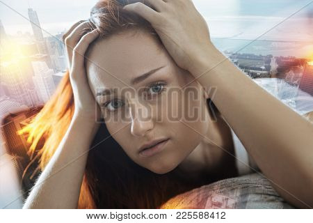 Sad woman. Upset young emotional woman feeling terrible and looking awful while resting on a sofa and touching her head poster