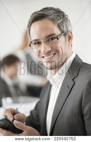 A Portrait Of Smiling Businessman Working With Smarphone