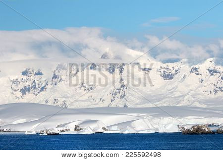 Antarctic Ocean, Antarctica. Glacier Snow Covered Mountain. Dramatic Blue Sky Background