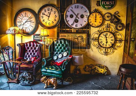 An Eccentric Vintage Living Room Armchairs With Many Clocks On The Wall Background In An Antique Sho