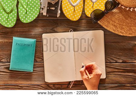 Planning a beach trip. Woman's hands with pencil over blank notebook. Travel items for beach tourism still life over wooden background.
