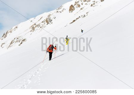 Two Ski Freerider Climbs The Slope Into Deep Snow Powder With The Equipment On The Back Fixed On The
