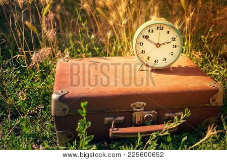 Blue Vintage Retro Alarm Clock On An Old Classic Brown Leather Suitcase On A Background Of Green Gra