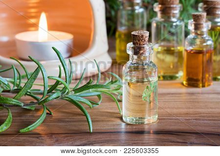 A Bottle Of Rosemary Essential Oil With Fresh Rosemary Twigs, With A Candle And Other Bottles In The