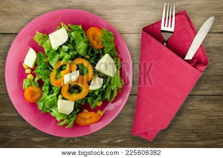 Salad Of Cheese, Lettuce, Corn, Pepper On A Wooden Background. Vegetarian Salad On A Plate. Vegetari