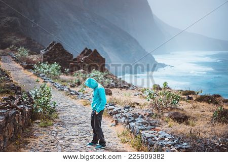 Tourist In Hoodie In Aranhas Valley Hiking From Cruzina To Ponta Do Sol. Huge Mountains Of Coastline