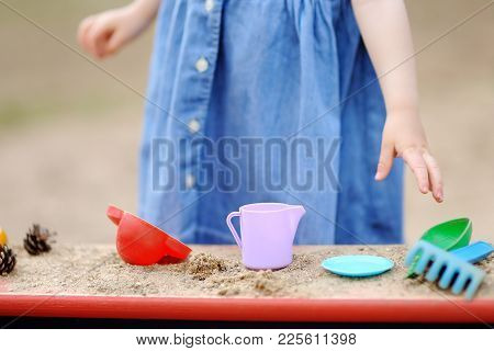 Cute Toddler Girl Playing In A Sandbox With Moulds And Pinecones. Outdoors Game For Little Kids. Dev