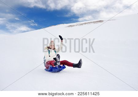 Happy Middle Age Woman Having Fun During Rolling Down The Mountain Slope On Sled In Alps. Winter Spo