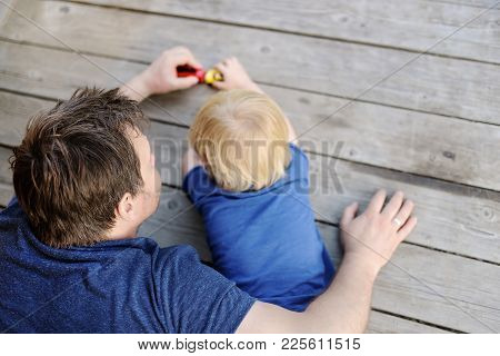 Unrecognizable Father With His Little Son Playing With Toy Cars. Fatherhood And Childhood Concept