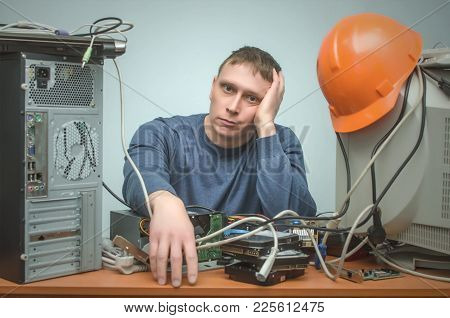 Tired And Bored Computer Repairman Is Sitting On His Workplace And Thinking. Computer Technician Tir
