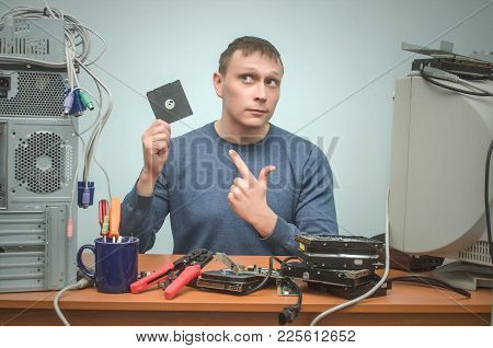 Computer Technician Engineer Is Holding In One Hand A Backup Diskette Disk And Is Showing On It By H