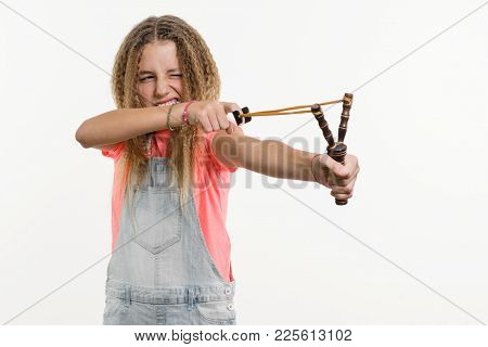 Naughty Girl Teenager With Curly Hair Holds A Slingshot. White Background Studio.