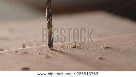 Electric driller on wooden plank
