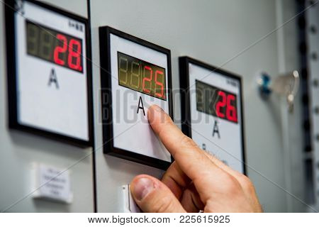 Man Hand On Ammeter Close-up. Control Of Energy System Parameters. Engineering Background.