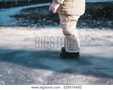The child is standing on the ice in the yard. Poor boy without skates