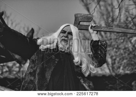 Brutal Druid Old Man With Long Silver Hair And Beard In Fur Coat With Axe In Hand On Blue Sky Backgr