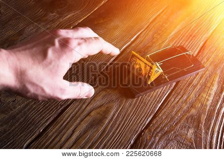 Man's Hand Stretches For A Banknote Which Is Bait In A Mousetrap. Copy Paste