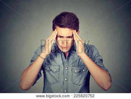 Stressed Man With A Headache Isolated On Gray Wall Background