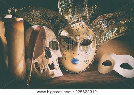 Theater And Drama Concept. Human Skull, Venetian Masks With Old Scroll Quill On Wooden Table