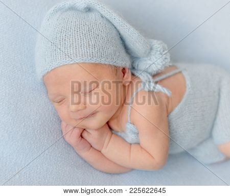 Smiling newborn baby boy sleeping peacefully.