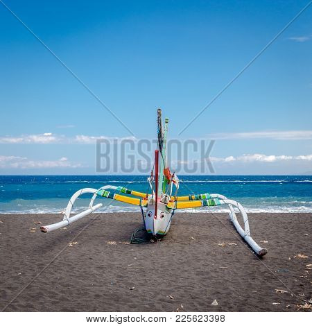Traditional catamaran boat, Bali Indonesia - black sand beach