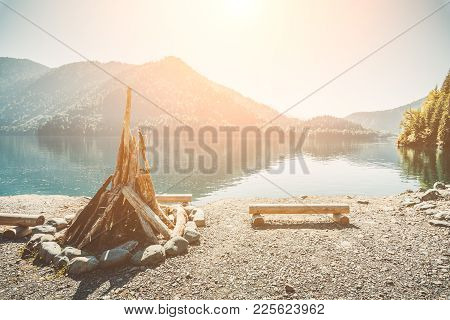 Prepared for kindling a large bonfire and benches from the logs on the shore of a beautiful lake wit