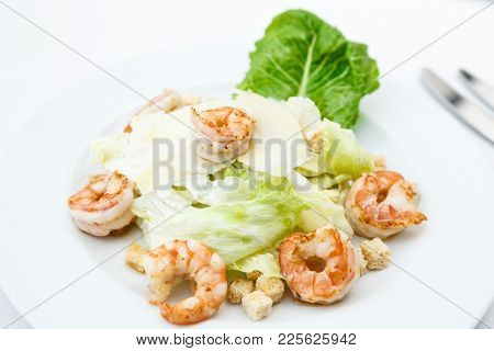 Classic Caesar salad with shrimps served on a plate