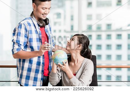 sian couple, woman and man, with globe and model airplane in urban apartment, symbolic picture for holiday planning and tourism industry