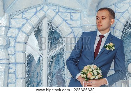 Portrait Handsome Groom In A Blue Suit Wait Bride In The Studio During A Photoshoot