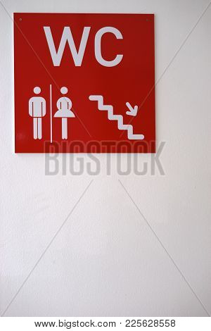 The Sign Of A Toilet Center For Women And Men On A Concrete Wall.