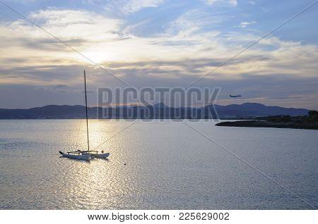 Mallorca, Spain - July 21, 2012: Catamaran Moored At Sunset And Jetliner Landing At Dusk On July 21,