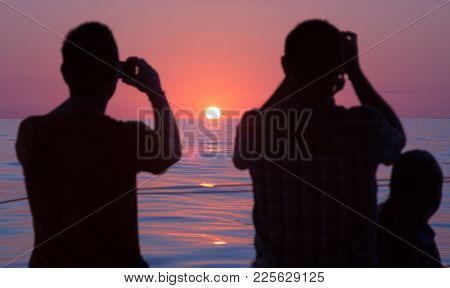 Palma, Mallorca, Spain On July 15, 2014: Two Men In Silhouette Photographing Sunrise At Sea On A Sun