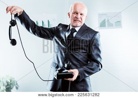 Upset Businessman Holding A Phone At Arms Length