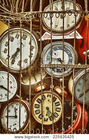 Old antique retro clocks in iron cage. Collection of vintage alarm clock. Lost time concept.