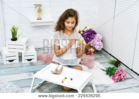Ten Years Girl Painting Eggs For Easter In Bright White Room