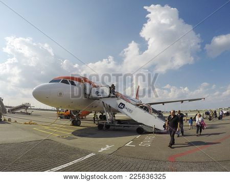 Amsterdam, Netherlands: January, 2015: Passengers Disembark An Easy Jet Airplane At Schiphol Airport
