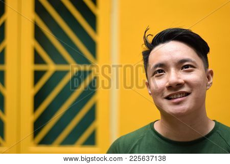 A Young Looking Handsome Asian Man Smiling