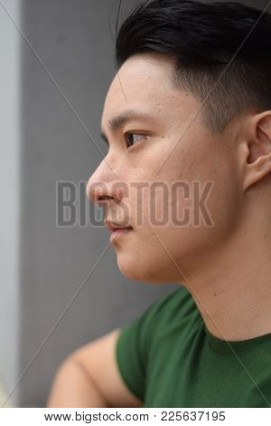 A Side Profile Of A  Young Handsome Asian Chinese Man Looking Sad