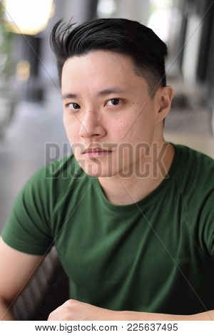 A Young Handsome Asian Man Looking At The Camera