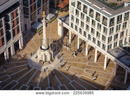 LONDON, UK - OCTOBER 30, 2012: Pedestrians crossing the Paternoster Square next to St Paul's Cathedral and London stock exchange (LSE) in the City of London