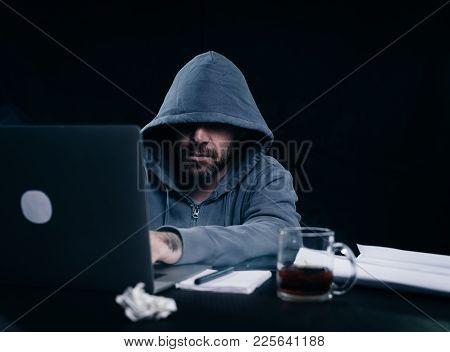 A Man Hacker In A Sweatshirt With A Hood Is Sitting At A Table And Something Is Typing In A Laptop