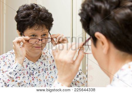 Senior Woman Trying On New Eyeglasses And Looking Over The Glasses At Herself In The Mirror