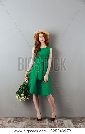 Photo of redhead young displeased woman in green dress and hat standing over grey wall background looking aside with flowers.