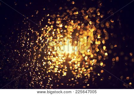 Bokeh Of Glitter Lights Black Background, Shining Defocused Abstract Lights. Gold Bubble Lights Or S