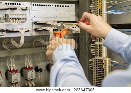 Screwdriver And Wire Cutters In Hands Of Electrician Against Electric Box With Terminal, Wires And C