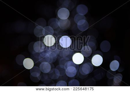 Bokeh Camera Lens Affect Of White And Grey Circles On A Dark Black Background