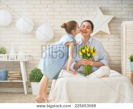 Happy mother's day! Child daughter is congratulating mom and giving her flowers tulips. Mum and girl smiling and hugging. Family holiday and togetherness.