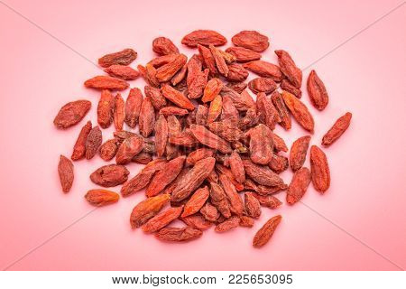 a small pile  of dried red Tibetan goji berries (wolfberry) against pink packground - superfruit