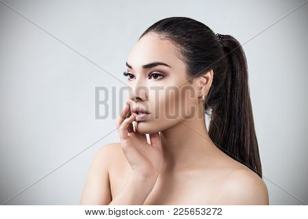 Portrait Of Young Sensual Woman With Perfect Skin. Over Gray Background.