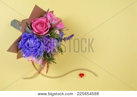 A Bouquet Of Colorful Paper Flowers And A Small Red Heart On A Yellow Background As A Backdrop For A